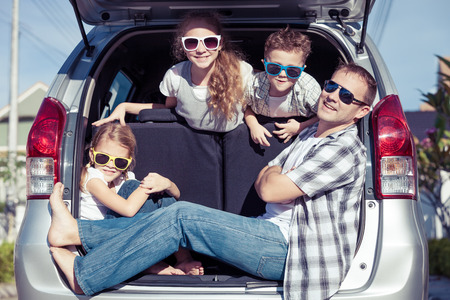 holiday trip: Happy family getting ready for road trip on a sunny day.  Concept of friendly family. Stock Photo