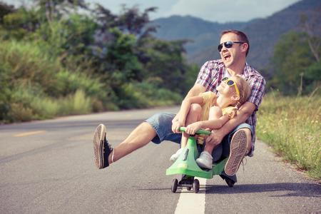 niñez: Padre e hija jugando en la calle, en el tiempo del día. Concepto de la familia. Foto de archivo