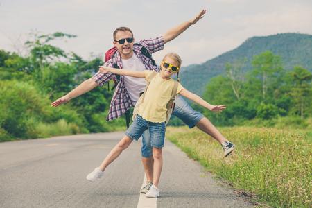 Vader en dochter lopen op de weg op de dag de tijd. Concept van de vriendelijke familie.
