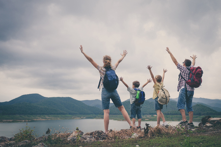 낮 시간에 호수 근처에 서 행복 한 가족입니다. 친화적 인 가족의 개념입니다. 스톡 콘텐츠