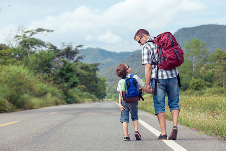 school boy: Father and son walking on the road at the day time.  Concept of friendly family.