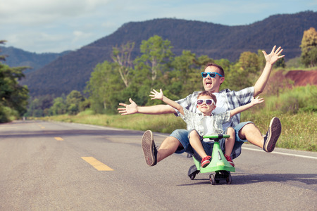love and friendship: Father and son playing  on the road at the day time.  Concept of friendly family.