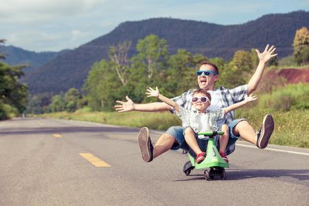 Vader en zoon spelen op de weg op de dag de tijd. Concept van de vriendelijke familie.