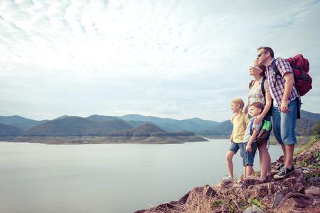 niño con mochila: Familia feliz de pie cerca del lago en el día. Concepto de la familia. Foto de archivo