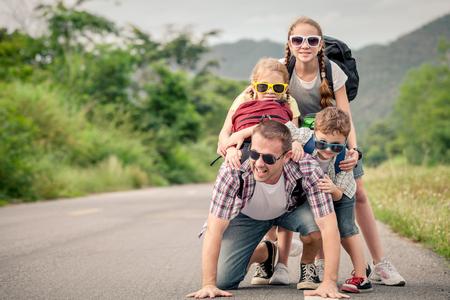 Père et enfants marchant sur la route au moment de la journée. Concept de famille sympathique. Banque d'images - 46976084