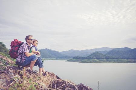 父と息子の一日の時間で湖の近くに立っています。 フレンドリーな家族の概念。 写真素材
