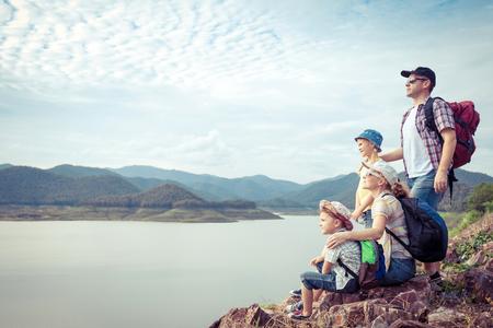하루 시간에 호수 근처에 서있는 행복 한 가족. 친절 한 가족의 개념입니다.
