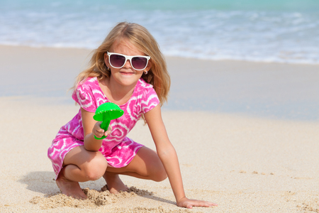 small girl: Happy little girl  playing on the beach at the day time Stock Photo