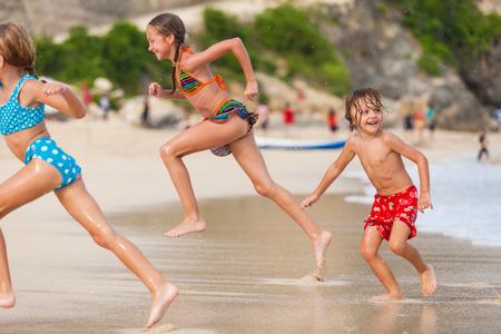 Drie gelukkige kinderen spelen op het strand van de dag de tijd. Stockfoto
