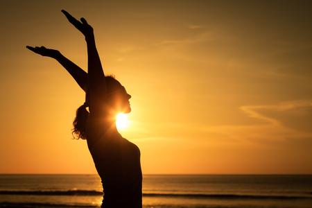 女性は、海に沈む夕日の下で腕を開きます。健康的な生活の概念。 写真素材