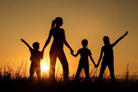 Šťastná rodina stojí v parku v době západu slunce. Koncepce přátelské rodiny.