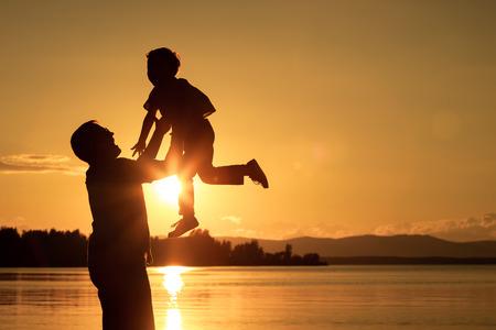 아버지와 아들은 일몰 시간에 산에 호수의 해안에서 연주입니다. 친화적 인 가족의 개념입니다.