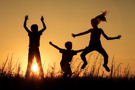 hermanos jugando: Felices los niños jugando en el parque a la hora del atardecer. Foto de archivo