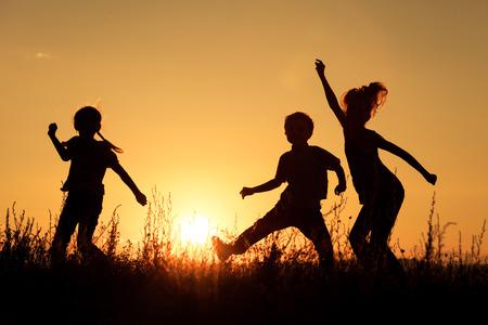 행복한 아이들이 일몰 시간에 공원에서 연주.