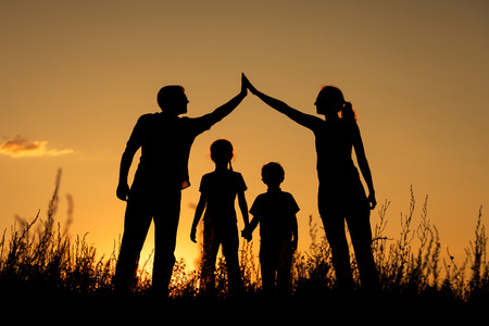 family on grass: Happy family standing in the park at the sunset time.  Concept of friendly family.