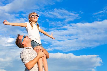 padre e hija: Padre e hija jugando en el parque en el día. Concepto de la familia. Foto hecha en el fondo de cielo azul. Foto de archivo