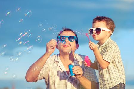 아버지와 낮 시간에 공원에서 노는 아들. 친화적 인 가족의 개념입니다. 푸른 하늘의 배경으로 그림.