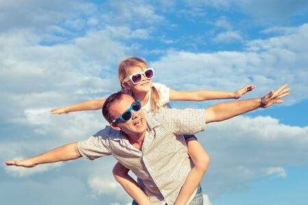 couple home: Father and daughter playing in the park  at the day time. Concept of friendly family. Picture made on the background of blue sky. Stock Photo