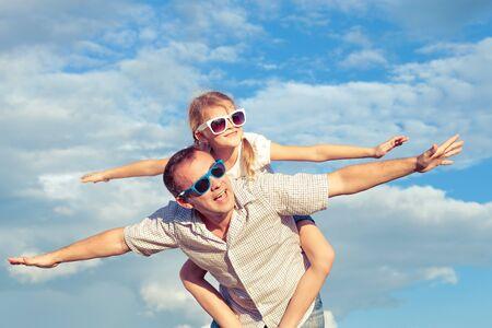 pareja en casa: Padre e hija jugando en el parque en el día. Concepto de la familia. Foto hecha en el fondo de cielo azul. Foto de archivo