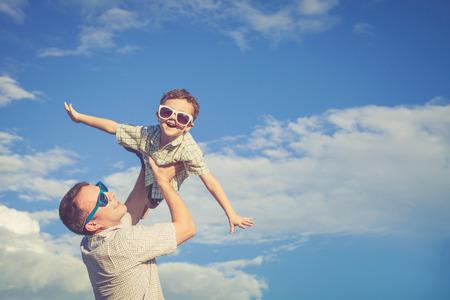 Vader en zoon spelen in het park op de dag de tijd. Concept van de vriendelijke familie. Foto gemaakt op de achtergrond van blauwe hemel. Stockfoto