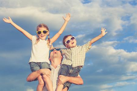 父と一日の時間に公園で遊んでいる子供たち。フレンドリーな家族の概念。写真は、青空を背景にしました。
