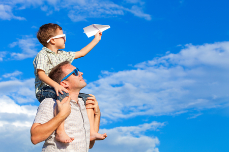 Father and son playing in the park  at the day time. Concept of friendly family. Picture made on the background of blue sky. Stockfoto