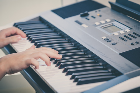 keyboards: Little girl playing synthesizer close up