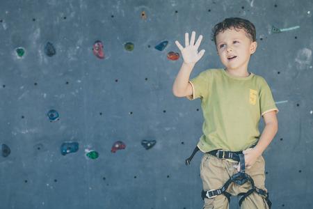 sports activities: little boy standing near a rock wall for climbing indoor