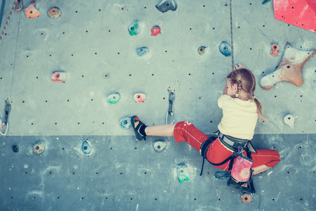 challenging: little girl climbing a rock wall indoor