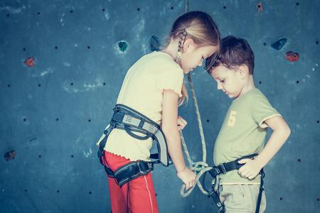 niño escalando: hermano y hermana de pie cerca de una pared de roca para escalar bajo techo Foto de archivo