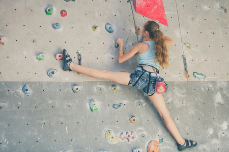 teenager climbing a rock wall indoor