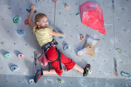 屋内の岩壁を登る少女 写真素材