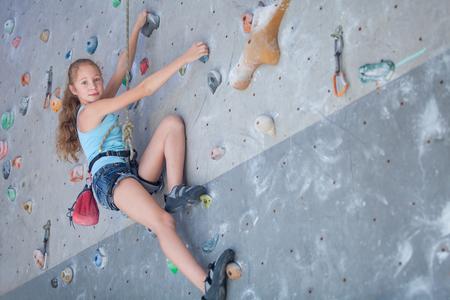 extremes: teenager climbing a rock wall indoor