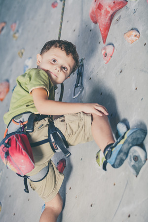 little boy climbing a rock wall indoor