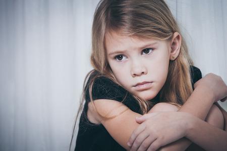 petite fille triste: Portrait de petite fille triste assis près de la fenêtre à la maison au moment de la journée Banque d'images