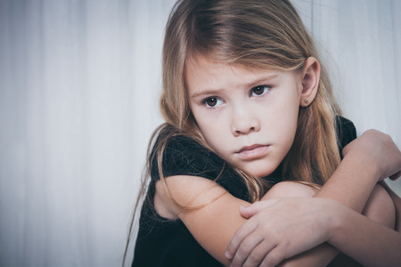 lonely: Portrait of sad little girl sitting near the window at home at the day time