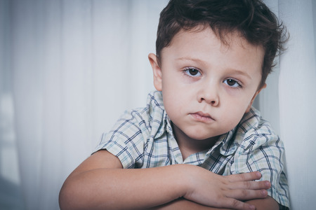 Portrait of sad little boy sitting near the window at home at the day time 版權商用圖片 - 47858670