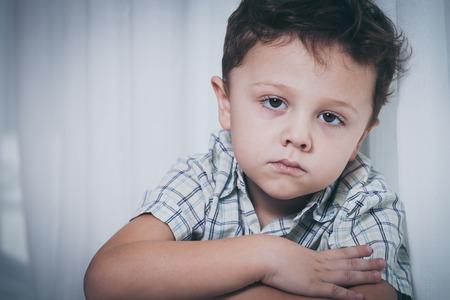 niños malos: Retrato del niño pequeño triste que se sienta cerca de la ventana en su casa en el momento día