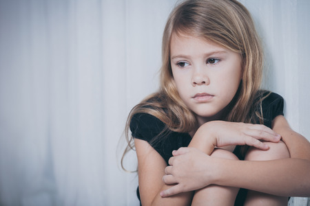 Portrait of sad little girl sitting near the window at home at the day time