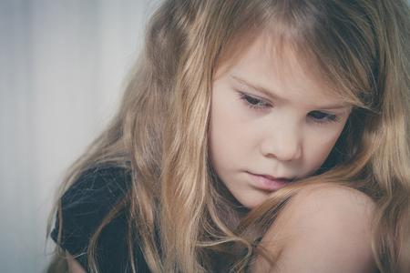 Retrato de la niña triste que se sienta cerca de la ventana en su casa en el momento día Foto de archivo - 47858677