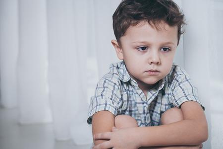 pardon: Portrait de triste petit gar�on assis pr�s de la fen�tre � la maison au moment de la journ�e