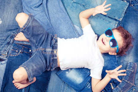 fashion boy: Cute little boy with sunglasses lying on the background jeans. Concept of denim fashion. Stock Photo