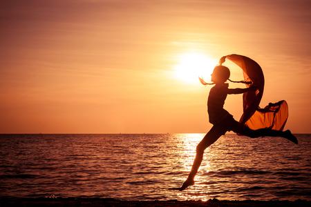 幸せな女の子の日没時にビーチでジャンプ