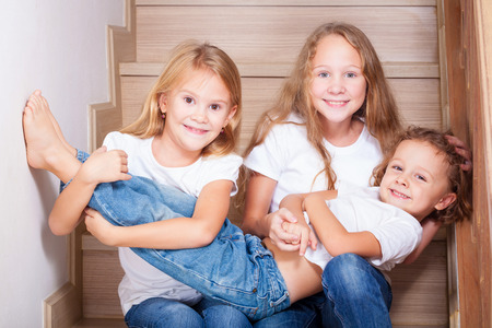 little  girls: Portrait of happy children which are sitting on the stairs in the house. The concept of a brother and sister forever.