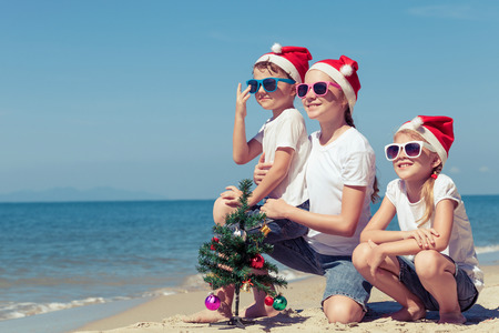 beach happy new year: Three happy children  playing on the beach at the day time. Concept of Happy New Year. Stock Photo