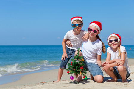 Three happy children  playing on the beach at the day time. Concept of Happy New Year. Stock Photo