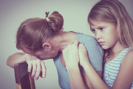 悲しい娘の家で彼の母を抱き締めます。夫婦家族の概念は、悲しみでです。