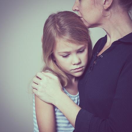 집에서 그의 어머니를 포옹하는 슬픈 딸. 부부 가족의 개념은 슬픔에 빠져있다.