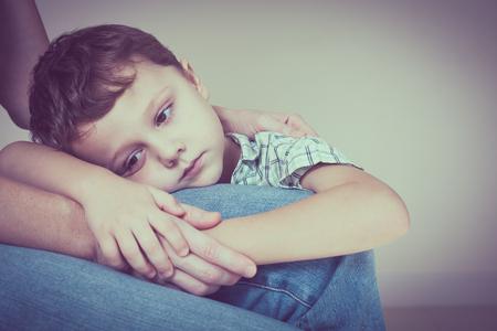 집에서 그의 어머니를 포옹하는 슬픈 아들. 부부 가족의 개념은 슬픔에 빠져있다.