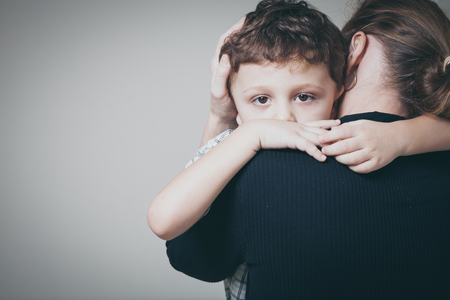 traurigen Sohn umarmt seine Mutter zu Hause. Konzept der familie ist in Trauer.